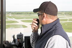 air traffic controller in an airport control tower, directing an airplane on a runway